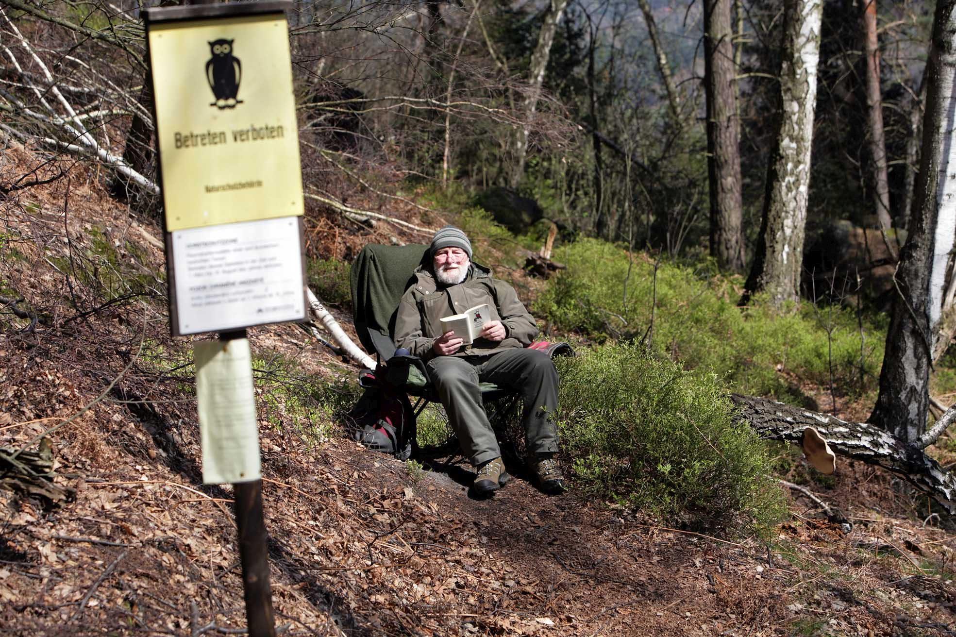 Ein Mann sitzt im Wald auf einem Stuhl.