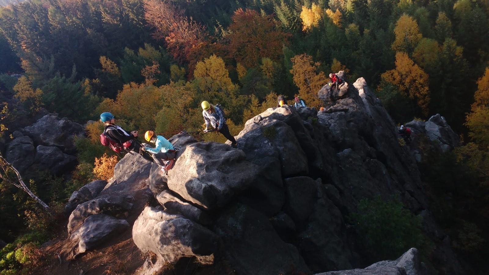Kids und Jugendleiter*innen bestreiten Klettersteig im Zittauer Gebirge, Im Hintergrund scheint Sonne in buntes Herbstlaub des Waldes
