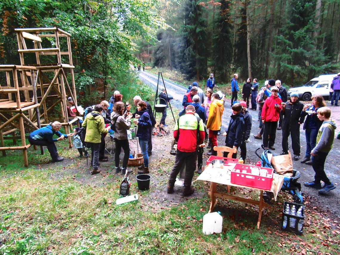 Viele Menschen stehen im Wald und unterhalten sich.