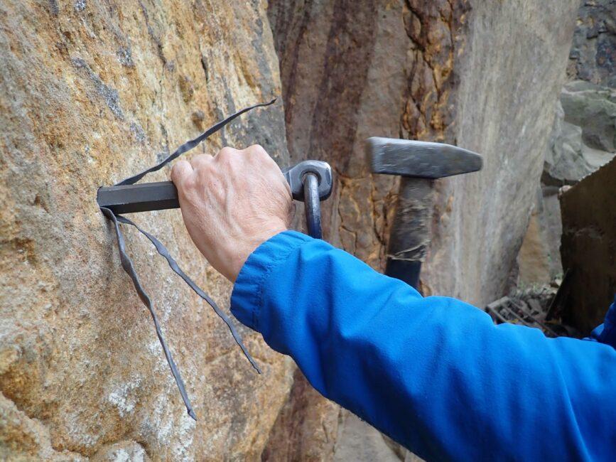 Eisenring wird mit Hammer in den Fels geschlagen