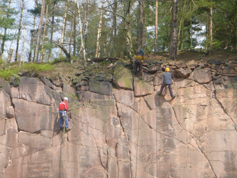 drei Kletterer arbeiten im Seil hängend in der Felswand