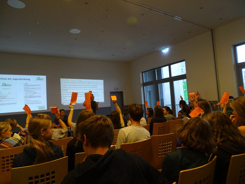 Kinder stimmen in Jugendvollversammlung mit Orangen Zetteln ab
