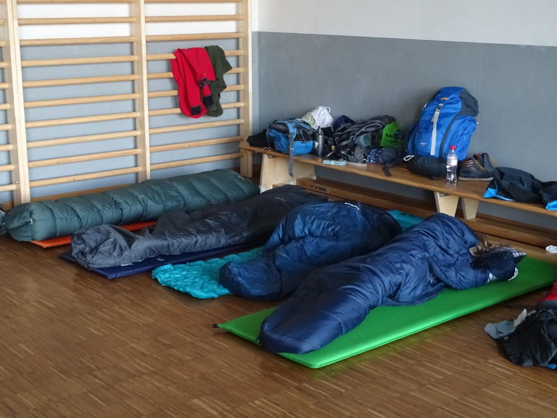 Vier Schlafsäcke und Isomatten in Sportraum als Schlafplatz