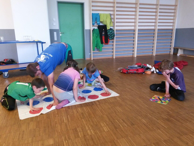 Kinder und Jugendleiter*innen beim Twister spielen