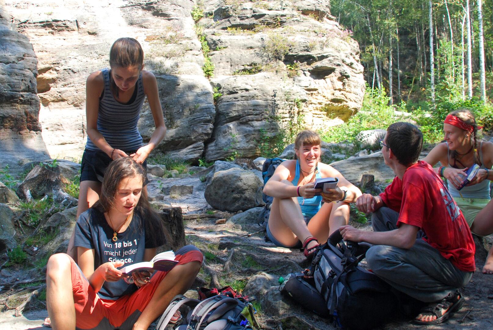 Jugendleiter*innen sitzen am Fuß von Felsen und sprechen über bevorstehende Kletterroute