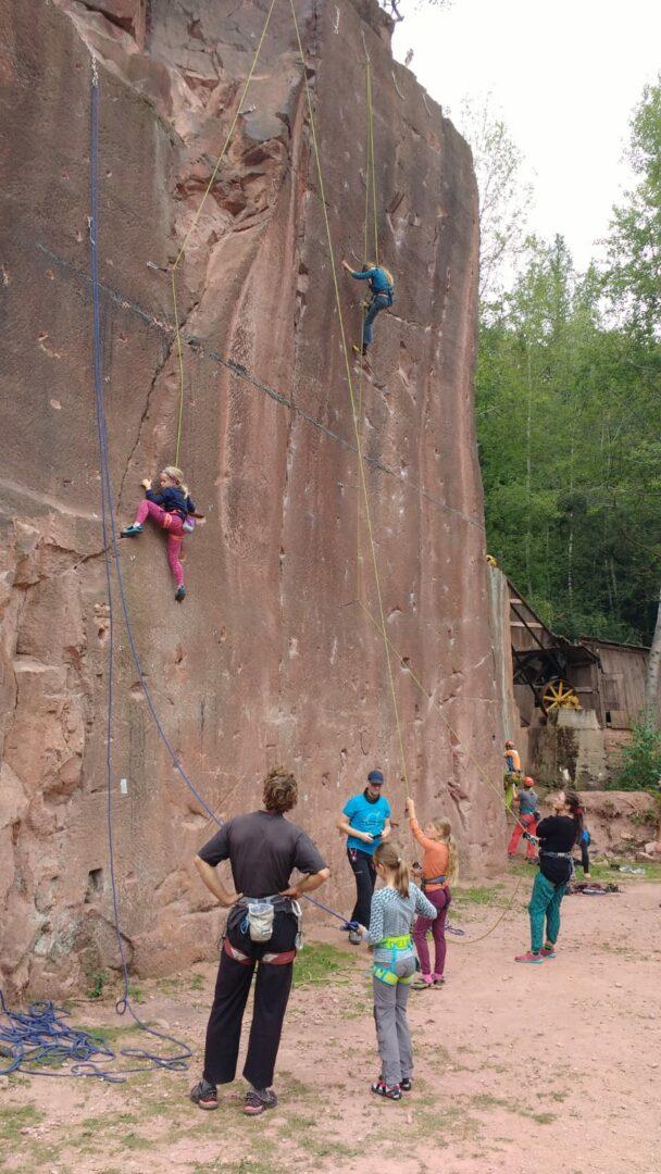 Kinder klettern im Nachstieg an Felsen Steinbruch, unten stehen Trainer*innen