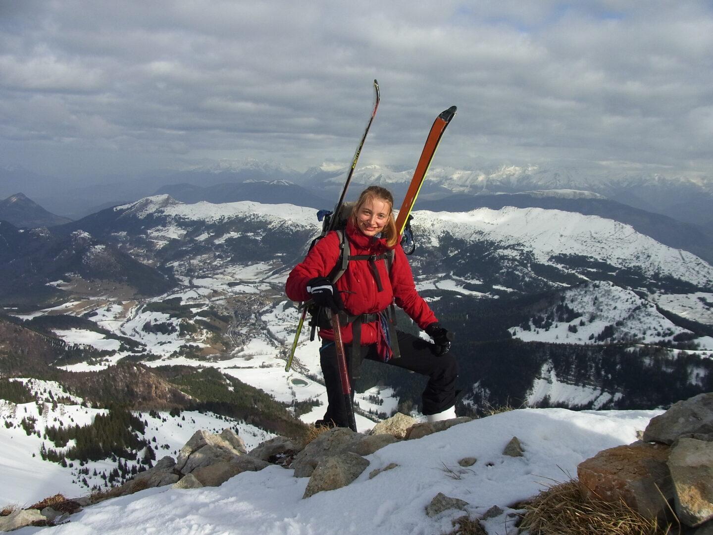 Eine Frau auf einem Berg mit Ski auf dem Rücken.