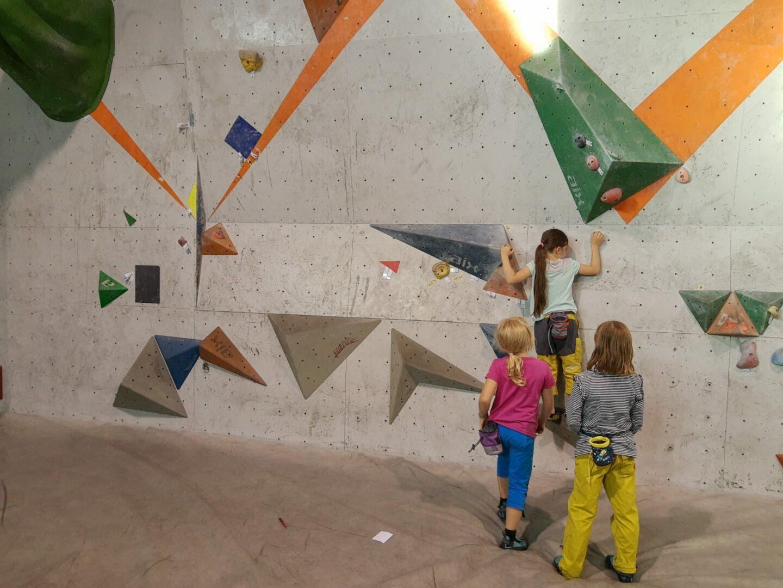 Drei kleine Kinder vor Boulderwand. Ein Mädchen bouldert die ersten Züge des Bouldern, die anderen grenzen Bereich ab